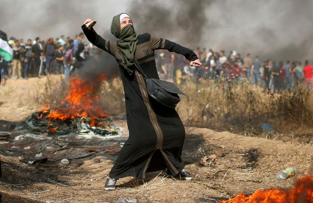 Palestina lança pedra durante protesto na Faixa de Gaza, nesta sexta-feira (13)  (Foto: Mohammed Salem/ Reuters)