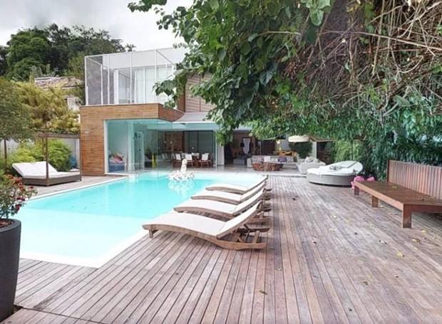 Um deck de madeira acomoda cadeiras de relaxamento próximas à piscina (Foto: EmCasa/ Reprodução)