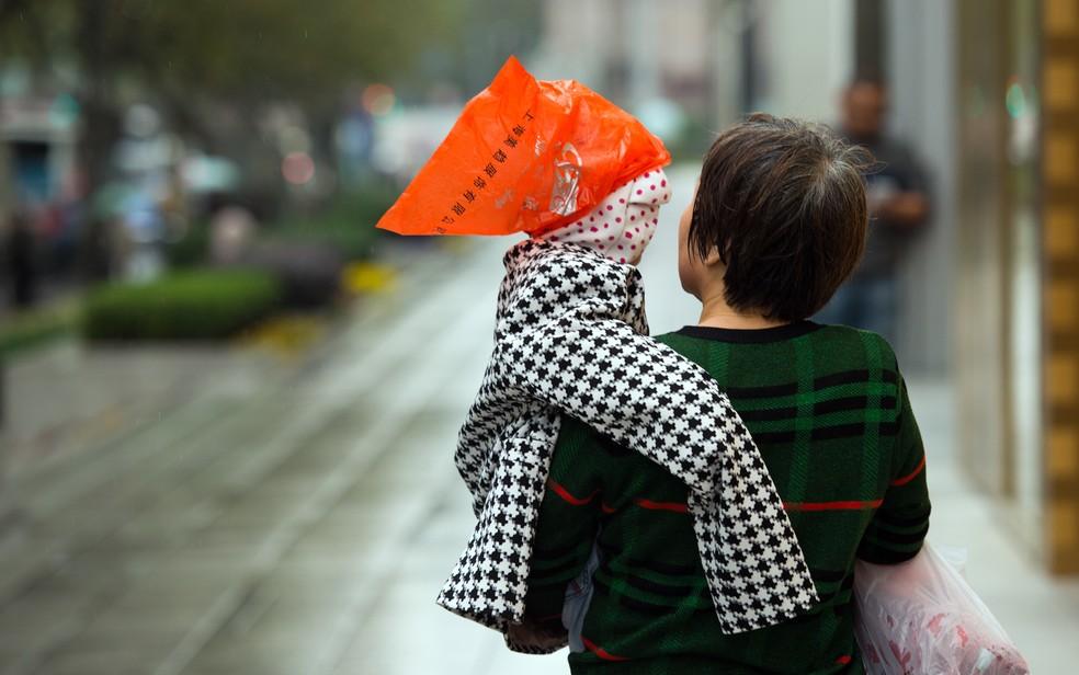 -  Uma mulher carrega um bebê coberto com uma máscara para protegê-lo da poluição e um plástico na cabeça para o proteger da chuva em Xangai, na China