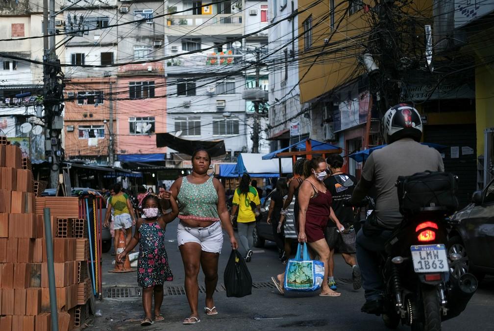21 de abril: mulher e criança andam de mãos dadas com máscaras protetoras contra a Covid-19 na Favela da Rocinha, no Rio de Janeiro. — Foto: Ricardo Moraes/Reuters