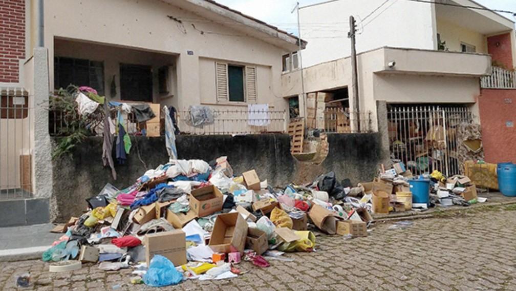 Parte do material que estava acumulado na casa foi jogada na calçada — Foto: Jussara Lima/Jornal Taperá