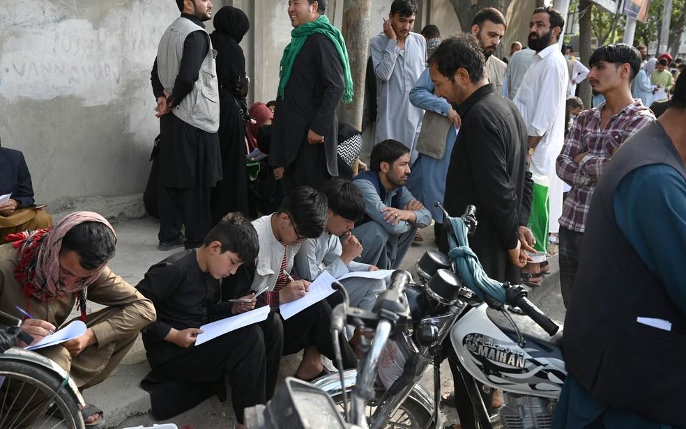 Afegãos preenchem seus dados em requisições para deixar o país em frente às embaixadas do Reino Unido e Canadá, em Cabul, na quinta-feira (19) — Foto: Wakil Kohsar/AFP