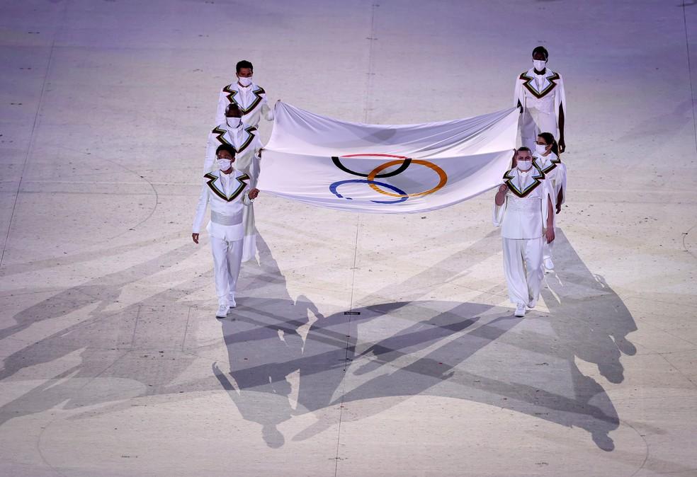 Atletas que também atuaram na linha de frente da pandemia carregam a bandeira olímpica — Foto: Cameron Spencer/Getty Images