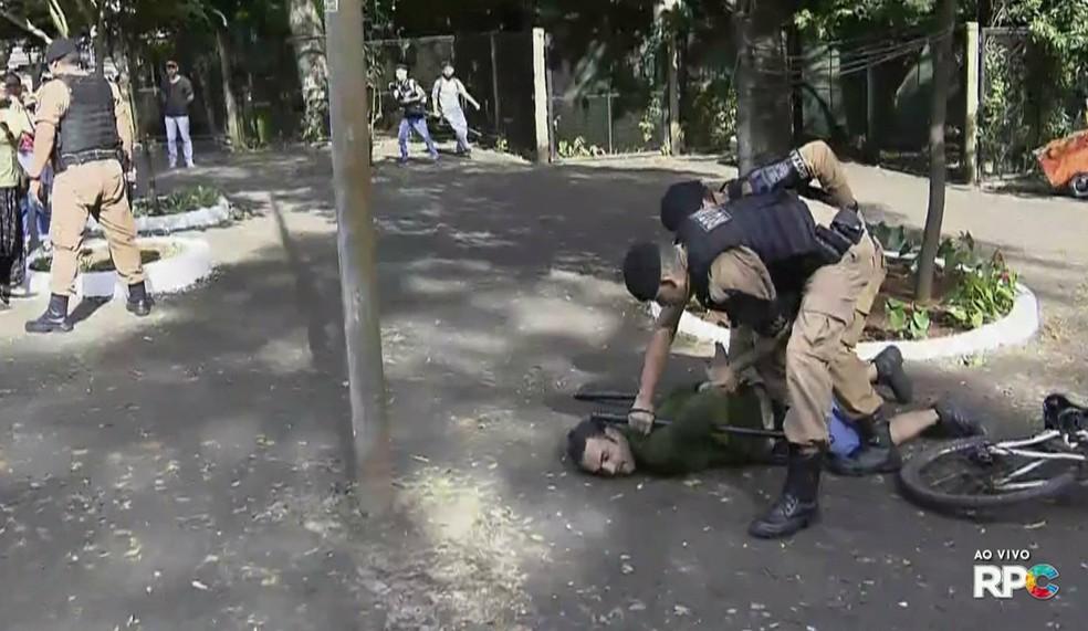 Um professor, que fazia parte de um grupo de manifestantes que tentava impedir a saída de ônibus do Terminal de Transporte Urbano (TTU), foi detido por policiais militares — Foto: Reprodução/RPC
