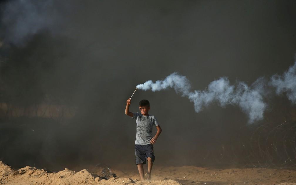 Menino palestino segura lata de gás lacrimogêneo lançada por tropas israelenses em Gaza, na sexta-feira (5) — Foto: Reuters/Ibraheem Abu Mustafa