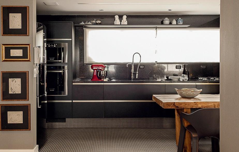 A cozinha tem bancada de mármore e armários da mesma cor. No corredor, quadros com pintura estilo bico de pena, de Itiberê Massulo. Apartamento do arquiteto paulista Ricardo Caminada