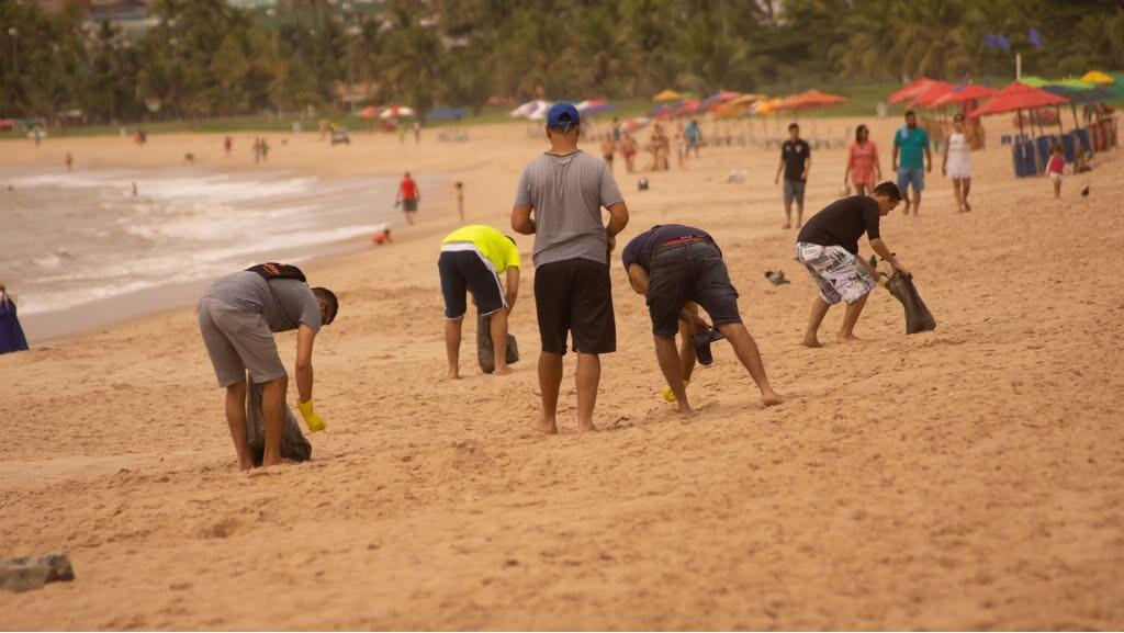 Voluntários fazem mutirão de limpeza na praia do Cabo Branco, em João Pessoa
