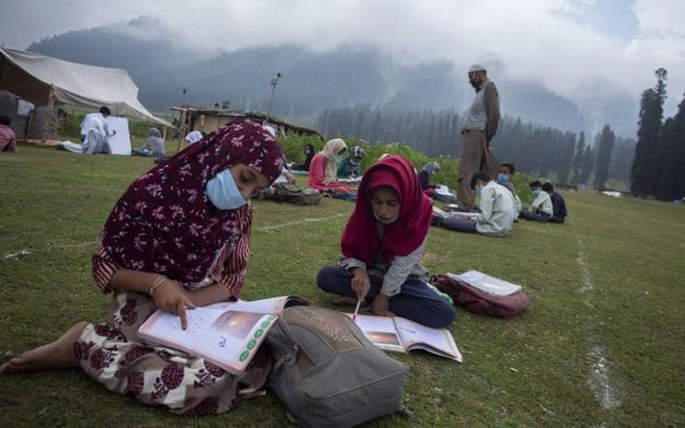 Mundo inteiro discute a retomada das aulas presenciais; acima, escola ao ar livre na Caxemira — Foto: BBC