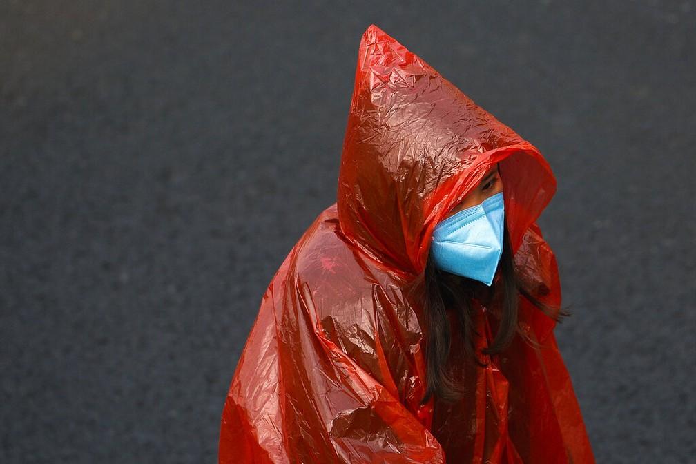 Mulher veste máscara e capa de chuva em Pequim para se proteger contra a epidemia de coronavírus — Foto: Andy Wong/AP