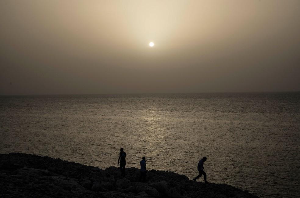 Pessoas assistem ao pôr do sol enquanto uma nuvem de poeira do Saara paira no ar em Havana, em Cuba, na quarta-feira (24)  — Foto: Ramon Espinosa/AP