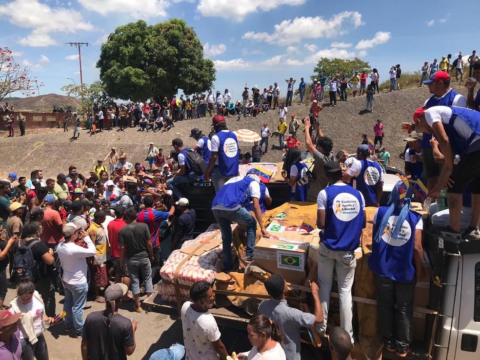 Em Pacaraima (RR), venezuelanos fazem cordão humano em torno de caminhão com doações de medicamentos e alimentos — Foto: Alan Chaves, G1 RR