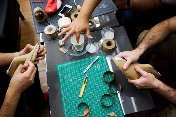 Quetzal Ramos, left, Jesus Garate, top, and Guy Perez, right, work on taping down plastic foot models in order to create a paper mold so that they may sketch on it, during the World Sneaker Championships workshop at Pensole Footwear Design Academy in Port (Foto: Marcus Yam)