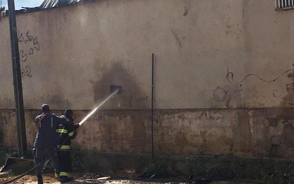 Bombeiros de Salvador fizeram buraco em um dos muros da fábrica para criar acesso para a mangueira de água — Foto: Phael Fernandes/G1