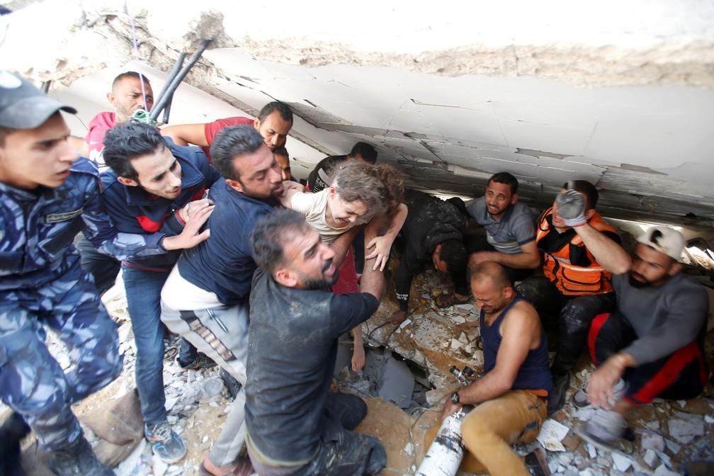 Equipes de resgate carregam Suzy Eshkuntana, de 6 anos, enquanto a puxam dos escombros de um prédio no local dos ataques aéreos israelenses na cidade de Gaza, no domingo (16)   — Foto: Mohammed Salem/Reuters