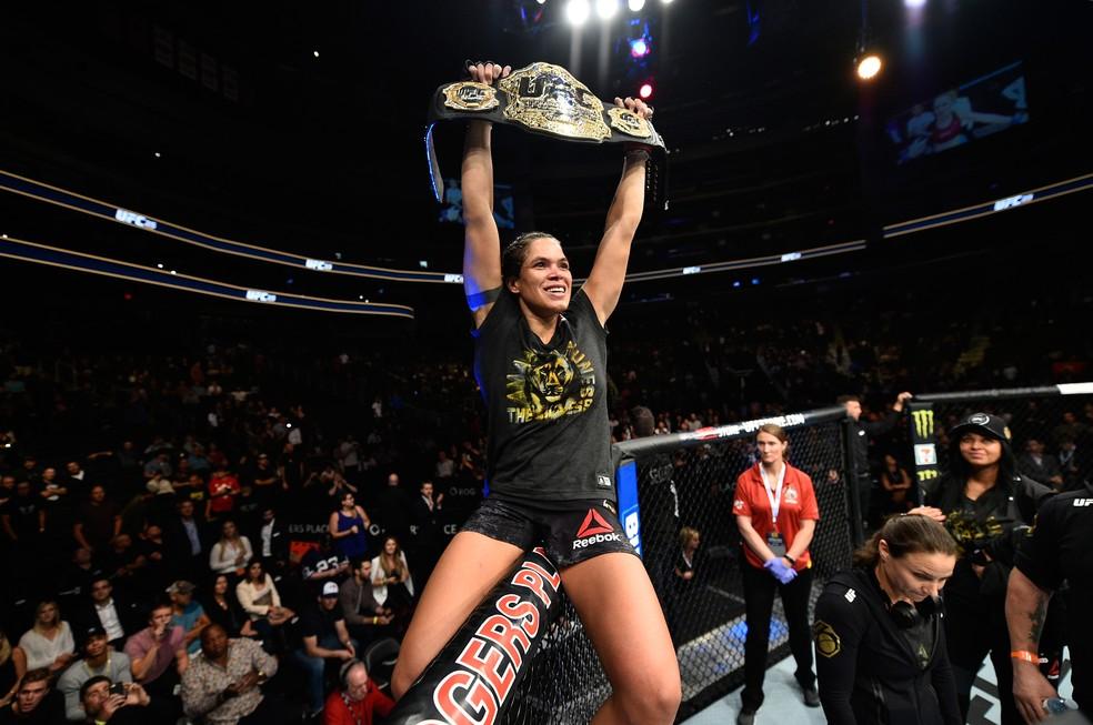 Amanda Nunes comemora sobre o octógono com o cinturão peso-galo no UFC 215 (Foto: Getty Images)