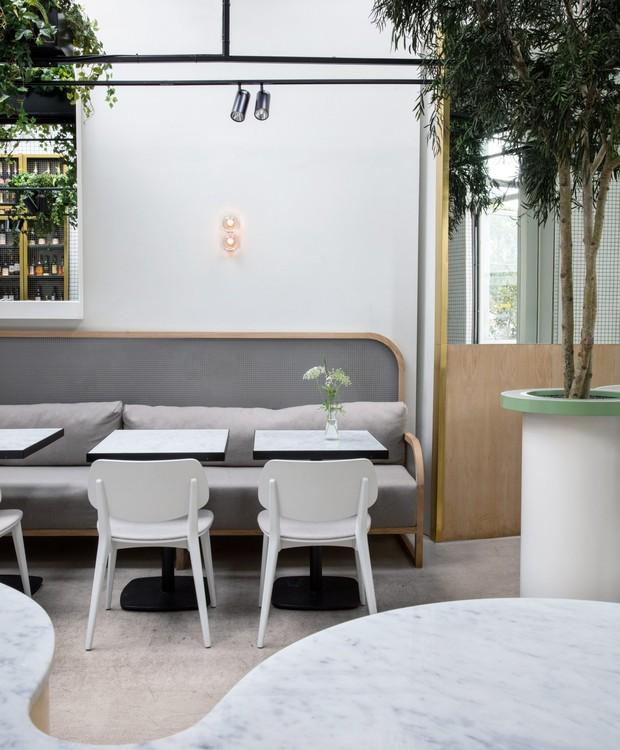 O verde das plantas traz vivacidade ao branco e cinza, muito presentes no café (Foto: Dezeen/ Reprodução)