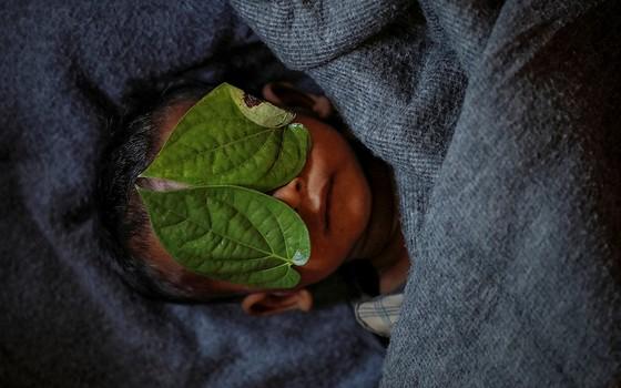 Folhas de betel cobrem os olhos de Abdul Aziz, de 11 meses, morto após ter febre alta no campo de refugiados de Balukhali, em Bangladesh (Foto: FOTÓGRAFOS/REUTERS)