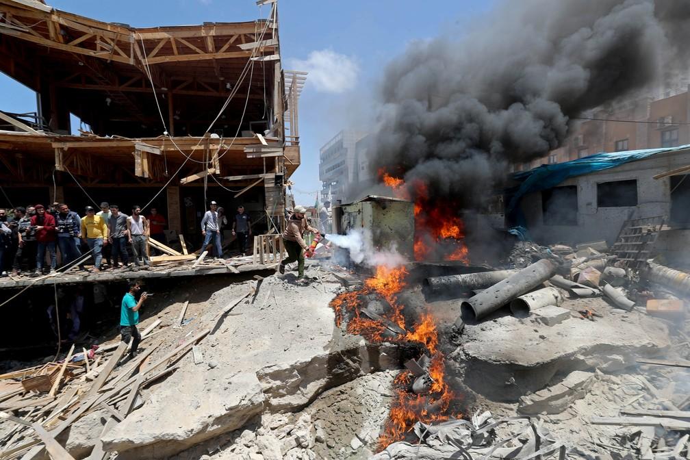 Um palestino tenta apagar um incêndio em escombros após ataques israelenses na Cidade de Gaza nesta segunda (17)  — Foto: Mohammed Salem/Reuters