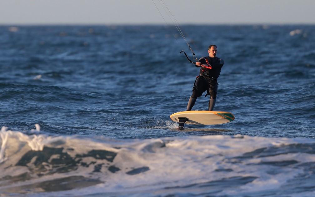 Homem pratica windsurf em New Brighton Beach, em Christchurch, na Nova Zelândia, no primeiro dia após o fim das regulamentações depois de o país ser declarado livre do coronavírus, na terça-feira (9) — Foto: AP Photo/Mark Baker