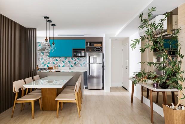 LIVING | Os azulejos da Lurca na parede da cozinha combinam com os armários azuis, desenhados pelas designers e executados pela Bontempo. A mesa em frente ao espelho é de acervo pessoal dos clientes. O piso de porcelanato no modelo Taiga da Portobello, é o mesmo em todos os ambientes para integrar ainda mais o espaço. (Foto: Renato Navarro / Divulgação)