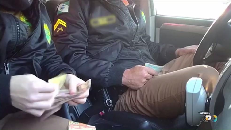Policiais rodoviários foram flagrados contando dinheiro de propina — Foto: Reprodução/RPC