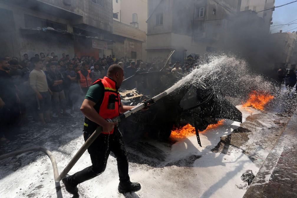 Membro da Defesa Civil Palestina apaga incêndio em carro do comandante do Hamas morto neste domingo (5) em Gaza — Foto: Ashraf Abu Amrah/Reuters