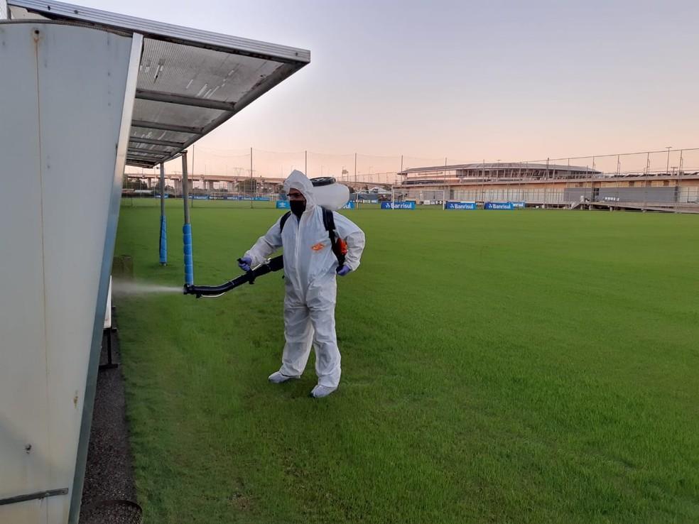 Profissional aplica produtos para descontaminação no campo de treinamento — Foto: Divulgação Grêmio FBPA