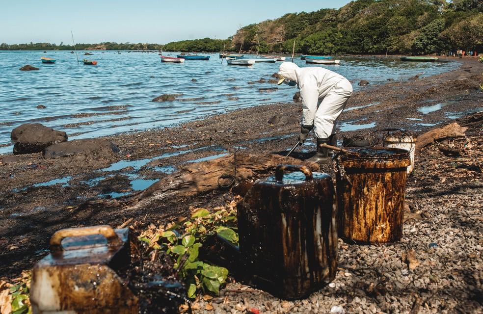 Um voluntário limpa óleo derramado do navio cargueiro japonês MV Wakashio que encalhou em um recife nas Ilhas Maurício, na quarta-feira (12) — Foto: Stephane Antoine/Reuters