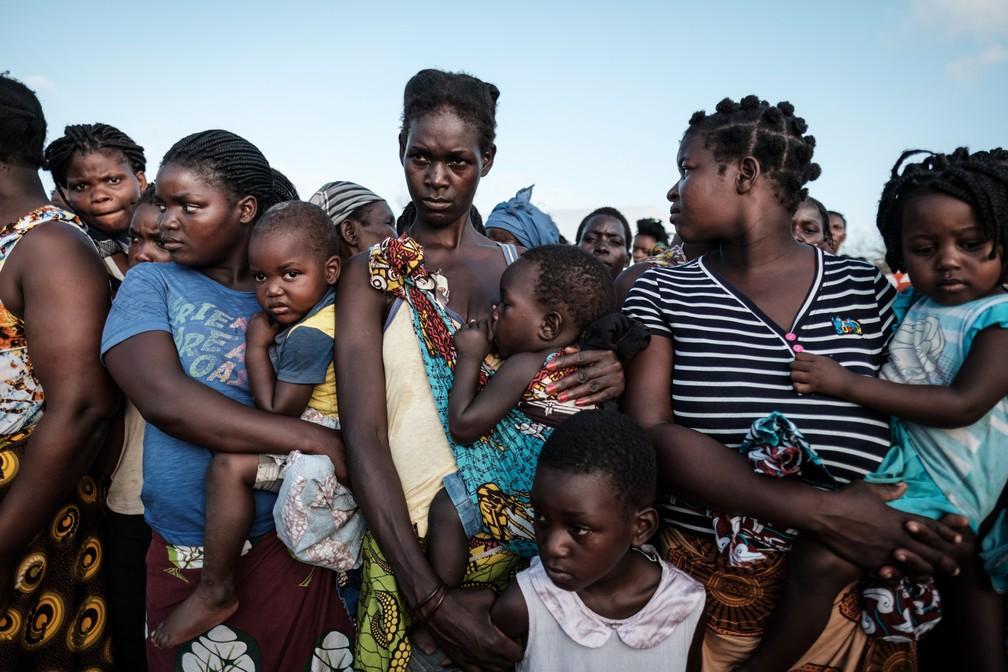 Mães esperam com os filhos para receber comida em frente a um centro distribuição em Dondo, a cerca de 35km de Beira, em Moçambique, nesta quarta (27). — Foto: Yasuyoshi Chiba/AFP