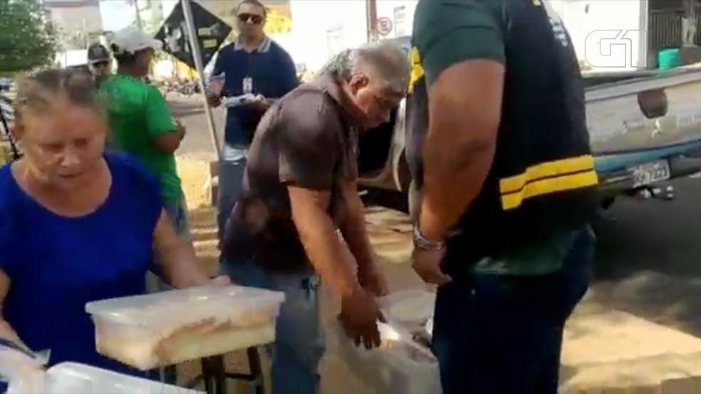 Imagem mostra fiscal da prefeitura recolhendo produtos — Foto: Divulgação