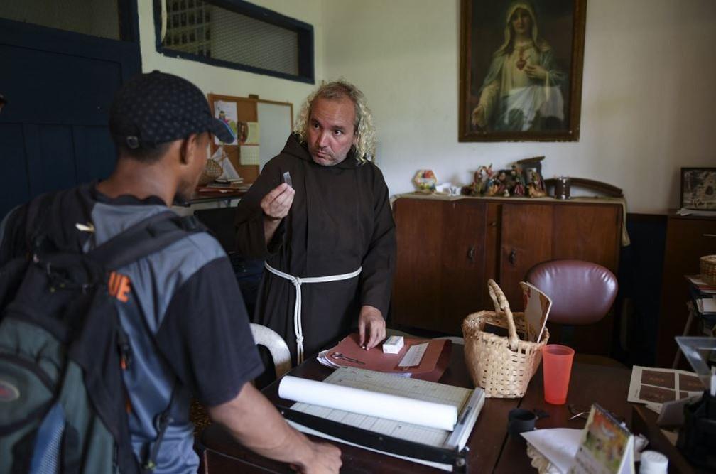 Frade capuchinho Nelson dá medicação a um indígena yukpa doente de malária em Los Angeles del Tukuko — Foto: Yuri Cortéz/AFP