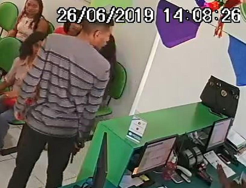 Homem segura uma arma na mão enquanto faz reféns pacientes e funcionários de uma clínica odontológica em São Paulo — Foto: Câmera de segurança
