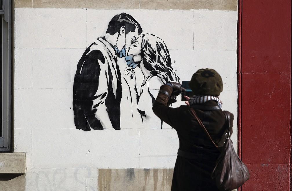 19 de março - Mulher fotografa um novo mural surgido na Bank Street em Glasgow, na Escócia, que mostra um casal abaixando as máscaras para trocar um beijo. De autoria do artista de rua conhecido como Rebel Bear, a obra é inspirada em barreiras provocadas ela pandemia do coronavírus — Foto: Andrew Milligan/PA via AP