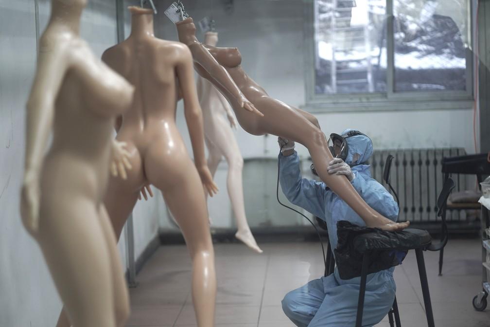 Homem finaliza pintura de uma das bonecas sexuais na China (Foto: Fred Dufour/AFP )