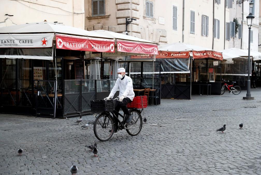 Entregador pedala pelo Campo dei Fiori, em roma, no primeiro dia em que restrição de deslocamento imposta pelo governo está em vigor — Foto: Remo Casilli/Reuters