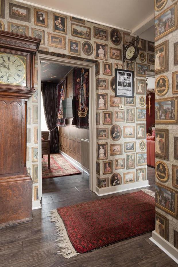 Corredor do apartamento de Harry Potter tem quadros inspirados no universo da série; na foto, um cartaz da vilã Belatriz Lestrange (Foto: Divulgação)