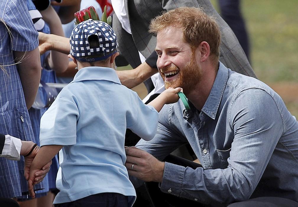 Menino de 5 anos brinca com a barba do príncipe Harry em Dubbo, na Asutrália — Foto: Phil Noble/Pool via AP