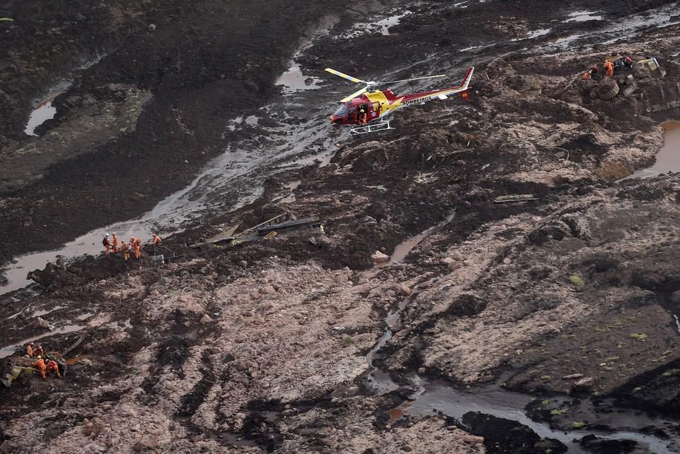 Helicóptero sobrevoa área do desastre do rompimento da barragem em Brumadinho, neste sábado (26) — Foto: Douglas Magno/AFP