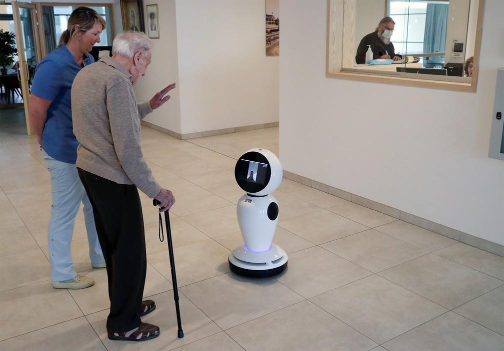 16 de março - Jozef Gouwy, de 93 anos, acena para alguém por chamada com vídeo graças a um robô em um abrigo de idosos de Ostend, na Bélgica. A empresa ZoraBots disponibilizou alguns robôs para casas de repouso, para ajudar os idosos a manterem contato com família e amigos durante período em que as visitas a esses lugares foram limitadas — Foto: Yves Herman/Reuters