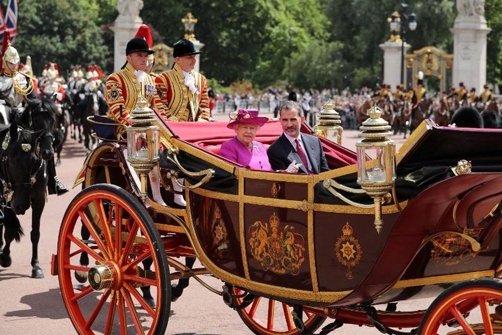 Rainha Elizabeth II e o rei espanhol, Felipe VI, chegam ao palácio de Buckingham de carruagem, nesta quarta-feira (12)  (Foto: Dan Kitwood / AFP)