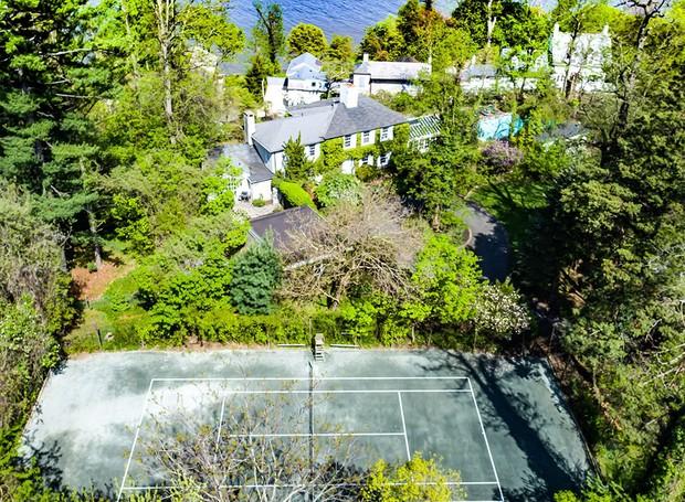 A área de lazer da casa conta com piscina e quadra de tênis (Foto: Ellis Sotheby's International Realty/ Reprodução)