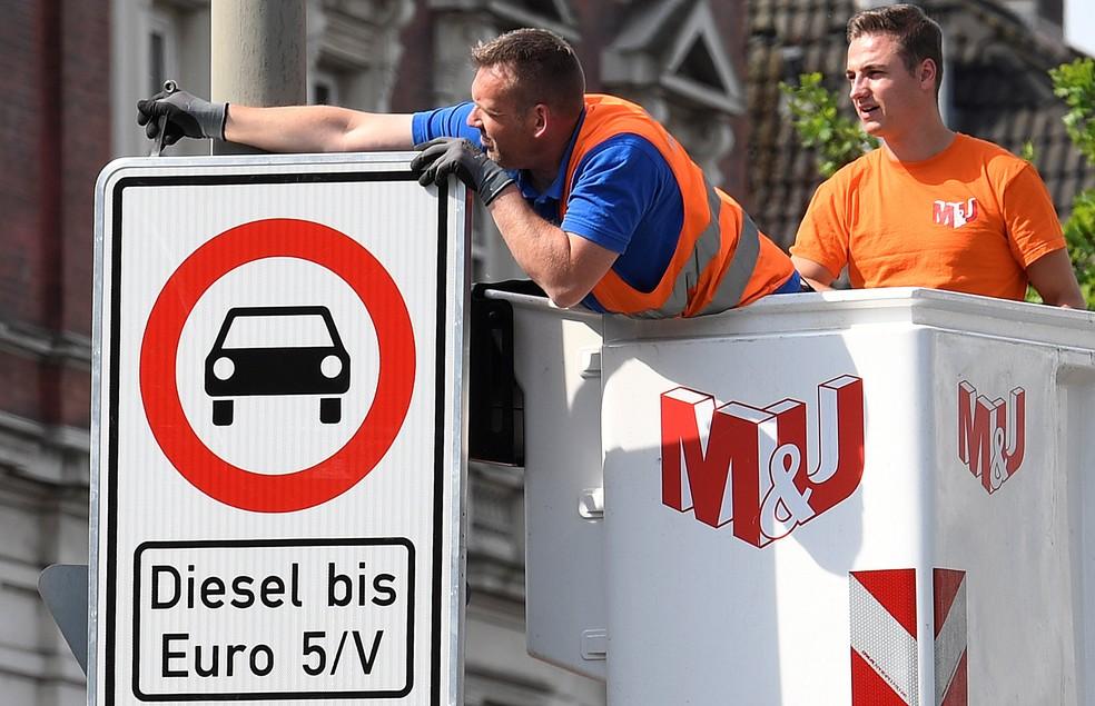 Funcionária instala placa que proíbe circulação de veículo a diesel (Foto: Fabian Bimmer/Reuters)