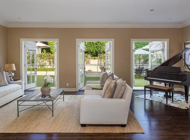 Uma sala de estar com piano leva ao jardim (Foto: Berkshire Hathaway HomeServices/ Reprodução)