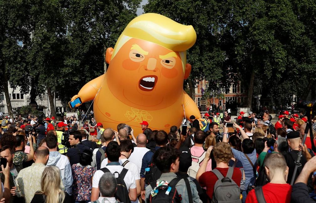 Manifestantes se reúnem em torno do 'bebê Trump' nesta sexta-feira (13) em frente à praça do Parlamento, em Londres  (Foto: Peter Nicholls/ Reuters)