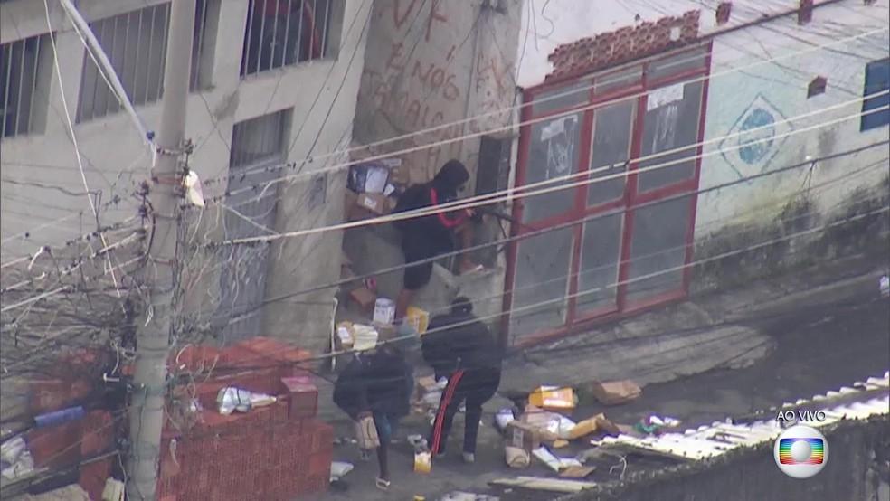 Homem aponta fuzil e dá cobertura para cúmplices no Morro São João, no Engenho Novo, na Zona Norte do Rio. (Foto: Reprodução/ TV Globo)