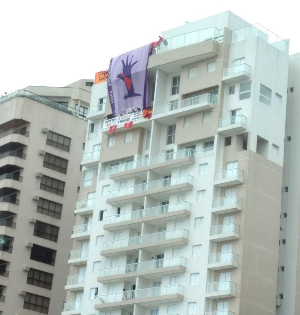 Militantes estendem bandeiras no triplex atribuído a Lula (Foto: G1 Santos)