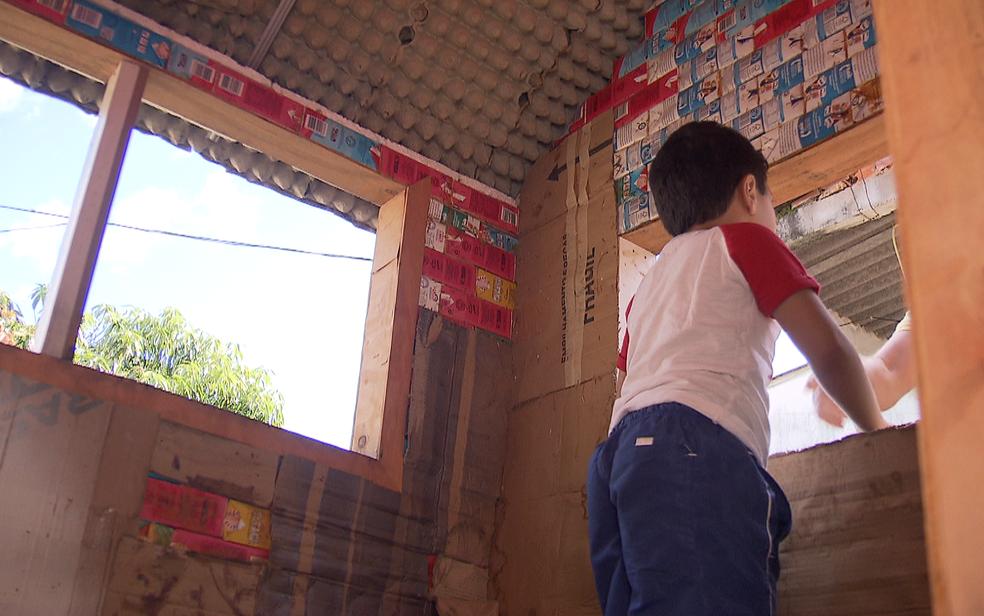 Criança de 5 anos brinca dentro de casinha de brinquedo feita de material reciclável em terreno em Sobradinho, no Distrito Federal (Foto: TV Globo/Reprodução)