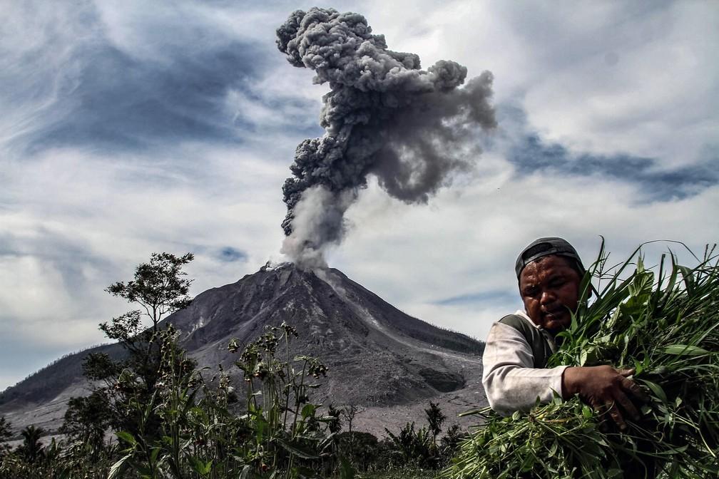 6 de janeiro - Um homem carrega sua colheita de vegetais enquanto o vulcão Sinabung solta densa fumaça, em Karo, na Indonésia  (Foto: Ivan Damanik/AFP)