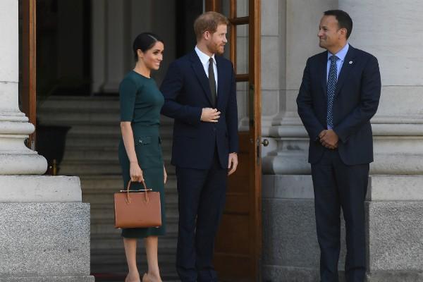 A atriz e duquesa Meghan Markle na companhia do marido e utilizado a bolsa ainda com o plástico (Foto: Getty Images)