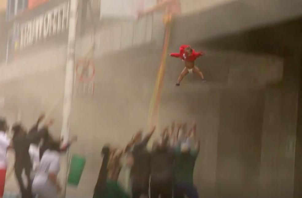 Criança é arremessada de prédios em chamas na África do Sul para ser resgatada — Foto: Reprodução/BBC